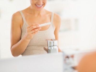 Kvinna tittar på positiv graviditetstest